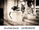 Aged photo of flower in watering can on wooden table  near window - stock photo