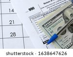 Small photo of Form 990 Return of organization exempt from income tax and blue pen with dollar bills lies on office calendar. Internal revenue service tax form