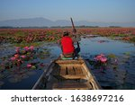 Rear view of man paddling Rowboat in the lake at thailand For tourist services.