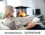 senior woman reading book at... | Shutterstock . vector #163960448