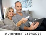 senior couple sitting in couch... | Shutterstock . vector #163960799