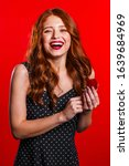 Small photo of Pretty european young woman holding small jewelry box with proposal diamond ring on red wall background. Girl smiling, she is happy to get present, proposition for marriage.