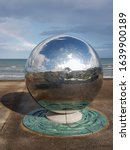Small photo of Newcastle, County Down, IRELAND - August 5h, 2019: A large reflective metal steel sphere sculpture on new promenade in Newcastle county down Northern Ireland