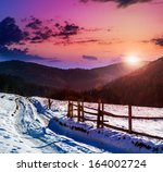 fence by the road to forest in the mountains on a fine winter sunset - stock photo