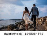 Young married couple walking along stony beach path holding hands with clouds emerging in the background