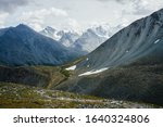 Trail through stony hills to beautiful huge glacier mountains under gray cloudy sky. Awesome dramatic alpine landscape with snow mountains and glaciers. Atmospheric highland scenery. Bad rainy weather - stock photo
