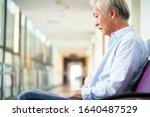 sad and devastated asian senior man sitting alone in empty hospital hallway, head down
