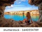 View from sea cave near Cape Greko(Capo Greco) of Ayia Napa and Protaras on Cyprus island, Mediterranean Sea. Attractive woman enjoys the sea air.