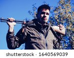 Closed and open hunting season. Man holding shotgun. Poacher with Rifle Spotting Some Deers. Illegal Hunting Poacher in the Forest - stock photo