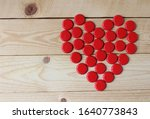 A red love heart made from beer bottle tops viewed top down on a rustic wooden table. Beer drinkers Valentine