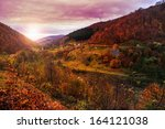 autumn landscape. village on the hillside. forest on the mountain covered with red and yellow leaves. over the mountains the beam of light falls on a clearing at the top of the hill. - stock photo