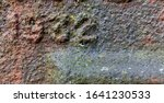 The year 1932 from a cast-iron inscription produced that year. Severely corroded and covered with lichen