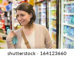 young woman buying a bottle of... | Shutterstock . vector #164123660