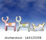 Two gingerbread reindeers and  sleigh with color icing shot on blue background - stock photo