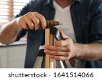 Small photo of Man burnishing edges of leather belt in workshop, closeup