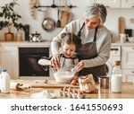 Small photo of happy family grandmother and granddaughter child cook in the kitchen, knead dough and bake cookies
