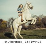 Portrait of young beautiful woman riding horse - stock photo