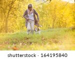 Stock photo senior woman walking her beagle dog in countryside 164195840