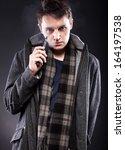 young man smoking electronic...   Shutterstock . vector #164197538