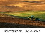 Tractor Plows A Field In The...