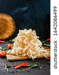 Small photo of Dried squid on wooden board on the black table background.