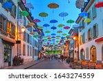 Night scene in Carouge, Geneva, Switzerland along Rue Saint Joseph covered by colorful umbrellas.