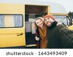 Young happy couple taking selfie in front of their yellow self-converted off-grid camper van - stock photo