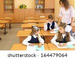 two girls and boy sit at wooden ... | Shutterstock . vector #164479064