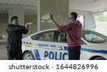Close up african american policeman with pistol arrest offender in mask stand hands up in patrol car in handcuffs burglar crime hold danger gangster gun robber illegal law bad guy slow motion - stock photo