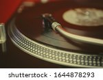 Small photo of Retro dj turntable player.Vinyl record under turntables needle.Professional audio equipment for hip hop dj.Listen to the music in hi-fi quality with vintage turn table device.Focus on tone arm
