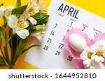 Small photo of April 2020 calendar, cute pure white easter eggs and white flowers on yellow background. April 2020 monthly calendar. Top view. View from above. Monthly April calendar