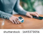 Small photo of Senior Woman Using Pulse Oximeter and Smart Phone, Measuring Oxygen Saturation