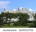 Small photo of Newport, Rhode Island-September 2017: Crossways Mansion built in 1896, partially hidden by thick trees.