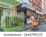 Small photo of Mexico City-November 29, 2019:street scene with colorful buildings and a street musician playing a windup music box