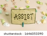 Small photo of Handwriting text writing Assist. Concept meaning help them to do a job or task by doing part of the work for them Colored crumpled papers empty reminder pink floor background clothespin.