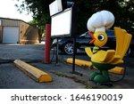 Small photo of Miami, Oklahoma - June 13 2015: The bird mascot at Waylan's Ku-Ku Burger, and menu sign, on Route 66.