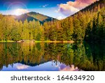 mountain lake near coniferous forest at the mountain foot - stock photo