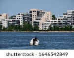 View of the modern residential district in Lahti, Finland. On the foreground man in his own boat on the lake. Apartments buildings near the water.