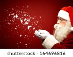 photo of santa claus blowing... | Shutterstock . vector #164696816
