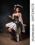Small photo of Young pirate female with long red hair. Woman is wearing a black corset bustier, tricorn hat , gun belt and armed with a pistol and sword.