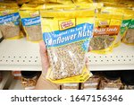 Small photo of Long Beach, California/United States - 02/12/2020: A hand holds a package of Good Sense sunflower nuts, on display at a local grocery store.