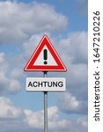 Small photo of A sign with a exclamation mark warning for a dangerous situation ahead and a smaller sign below with the German word Achtung on it, meaning danger in English