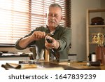 Small photo of Man burnishing edges of leather belt in workshop