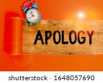 Small photo of Handwriting text writing Apology. Concept meaning a written or spoken expression of one s is regret remorse or sorrow Alarm clock and torn cardboard placed above a wooden classic table backdrop.