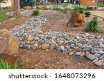 Landscaping with a dry stream and using river rock to accent garden