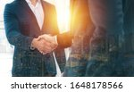 Small photo of Handshake of 2 businessman in a black suit double exposure the business center city.mergers and acquisitions for start greeting with good etiquette negotiation the success of both