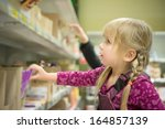 adorable girl select chocolate... | Shutterstock . vector #164857139