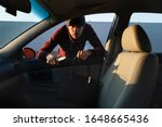 A man attacked a defenseless woman in a parking lot, he is trying to take her purse from her. - stock photo