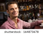 man with a cup of coffee at the ... | Shutterstock . vector #164873678