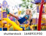 Small photo of Child on swing playing on outdoor playground. Kids play on school or kindergarten yard. Active kid swinging. Healthy summer activity for children. Little boy having fun outdoors.